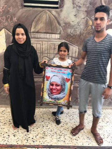 Children of Abeer Abu Jayyab hold a picture of their mother who died in 2017 after being repeatedly denied a permit to travel for breast cancer treatment.