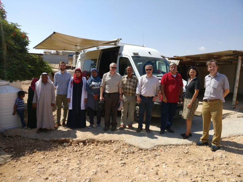 MPs, ICS staff and Trefaat community members in front of the mobile clinic