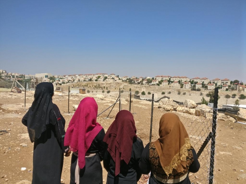 Women from Abu Nuwar look out at Ma'ale Adumim settlement